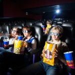 Siblings having snacks while watching 3D movie in cinema theater