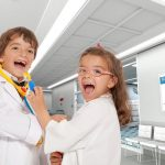 Little boy and girl playing doctors at the hospital